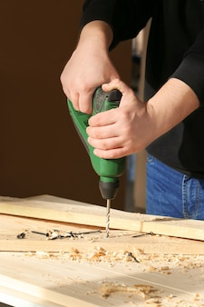 Плотник сверлит отверстие в деревянной доске на рабочем месте