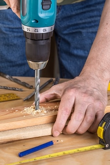 Carpenter drilling wood using portable drilling machine