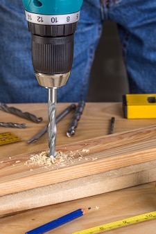 Carpenter drilling wood using portable drilling machine.