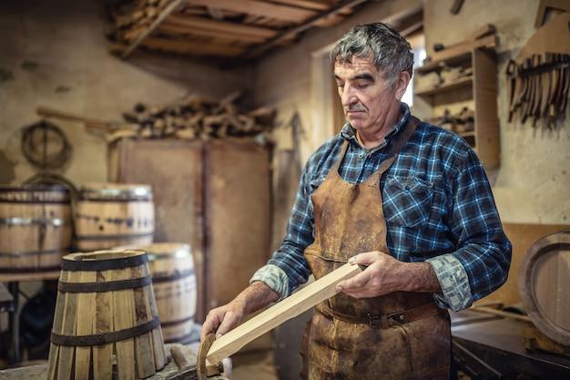 목수는 작업장에서 나무 통을 만드는 데 사용할 목재의 품질을 평가합니다.