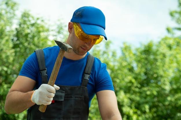 Плотник забивает гвоздь в деревянную доску, стоя на улице