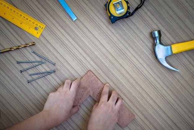 Carpenter hands measuring wood plank with a set collection of working hand tools for the wooden, toolset with the do it yourself (diy)