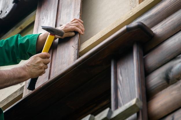 Carpenter handyman hammering a nail in wooden board.