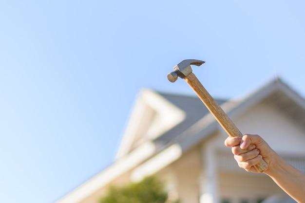 Карпентер держит молот перед домом для ремонта.