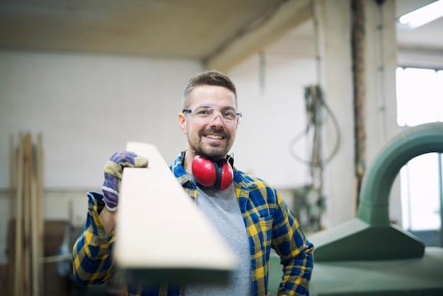 Плотник держит доску в деревообрабатывающей мастерской