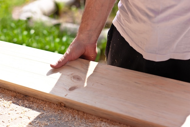 Carpenter holding wooden board