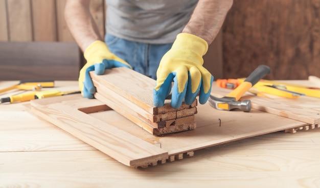 木の板を持っている大工。木工業