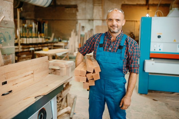 Carpenter holds stack of wooden beams, woodworking, lumber industry, carpentry.