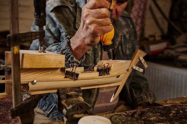 Плотник в действии, образ жизни, концепции хобби. мастер наклеивает деревянные детали на парусник в собственной мастерской.