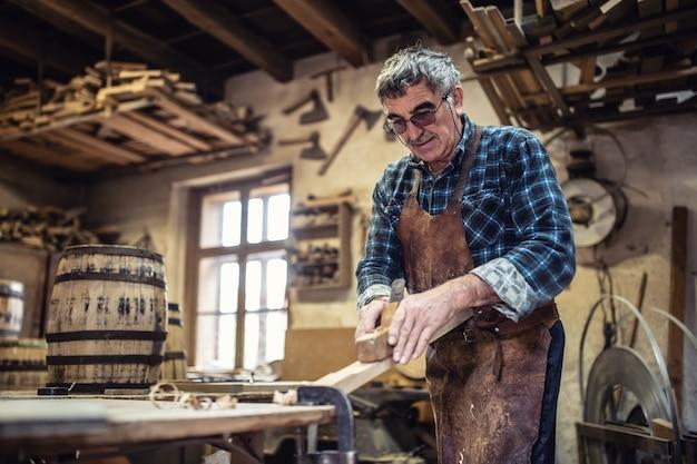 안경을 쓴 목수는 작업장에서 나무 표면을 매끄럽게 하기 위해 잭 플레인을 사용합니다.
