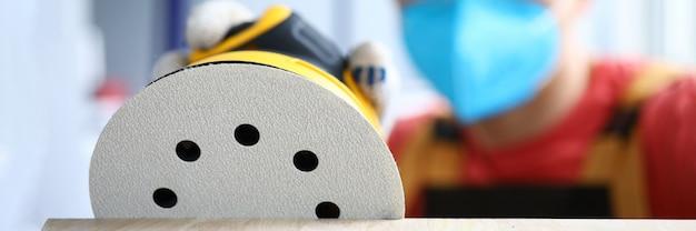 Плотник в защитной маске шлифует с помощью инструмента
