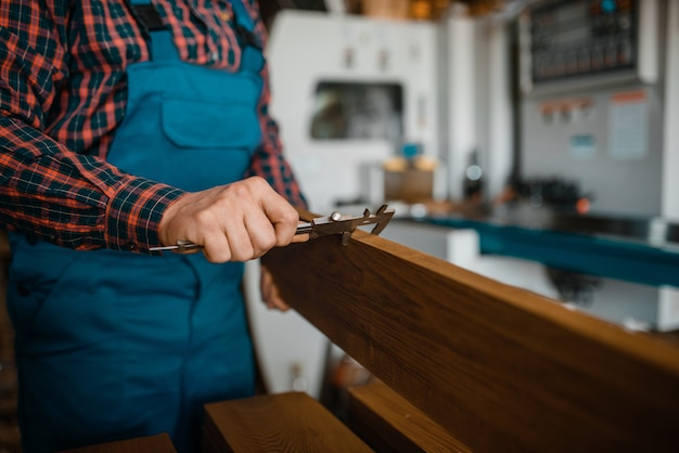 Плотник в униформе измеряет доску штангенциркулем, деревообрабатывающий станок, деревообрабатывающая промышленность, столярные изделия. обработка древесины на заводе, распиловка леса на складе