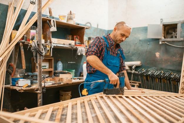 Плотник в униформе, деревообработка, деревообрабатывающая промышленность, столярные изделия. обработка древесины на мебельной фабрике, производство изделий из натуральных материалов.