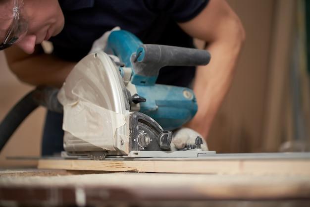 Плотник в белых перчатках работает над лобзиком