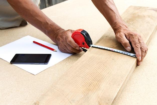Плотник проверяет качество материала и рассчитывает необходимое количество для производства.