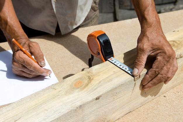 Плотник проверяет качество материала и рассчитывает