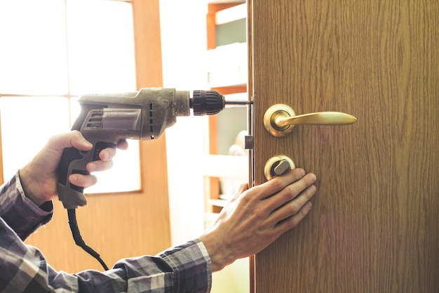 Carpenter installs a lock in a wooden door spinning the screw with a drill.