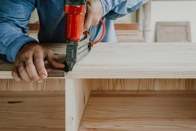 The carpenter is  making furniture the furniture