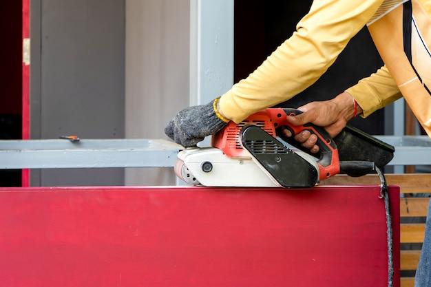 カーペンターは屋外のフィールドで彼のシェービングマシンによって赤い木製のドアを剃っています