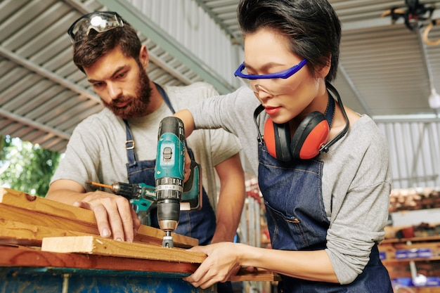 Carpenter looking at drilling coworker
