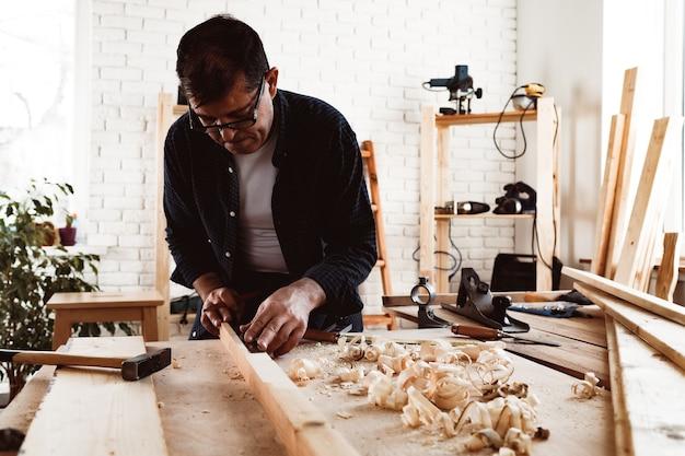 목수는 나무 판자에 연필 자국을 만든다.