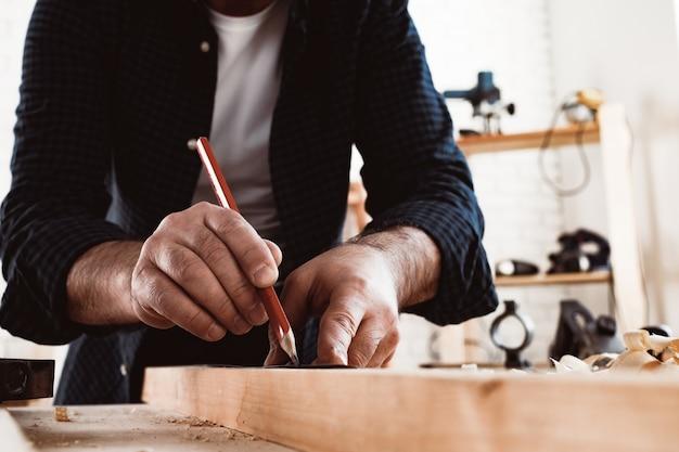 목수는 나무 판자에 연필 자국을 만든다