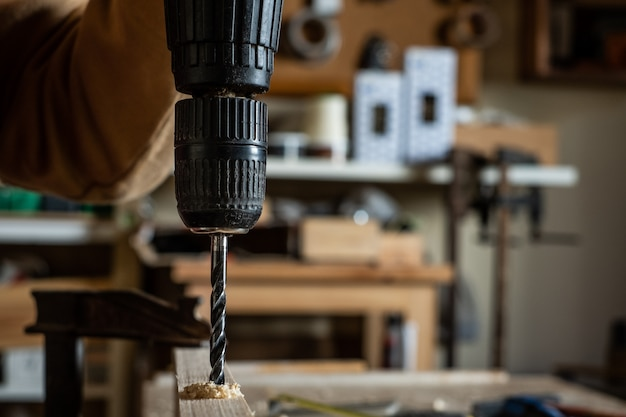 Плотник делает дрель с волчком на деревянной доске