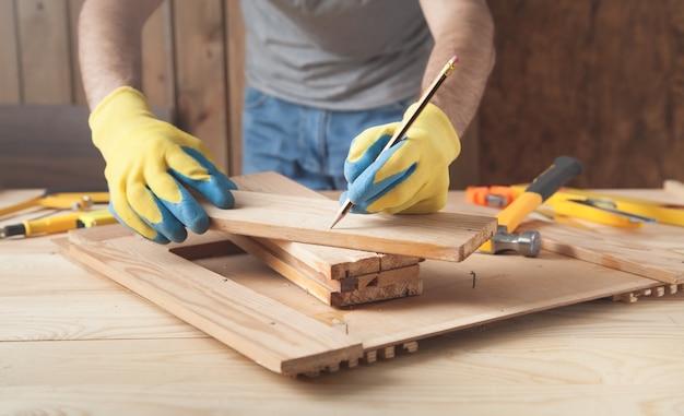 鉛筆で木の板に印をつける大工。