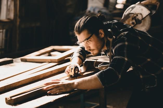 大工の男は、木の工房で傑作の木工品手作り家具を細かく作ることに出席します。