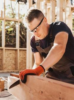 Плотник режет деревянную доску