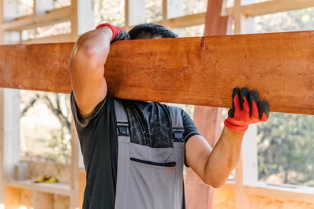 Carpenter man holding a big plank