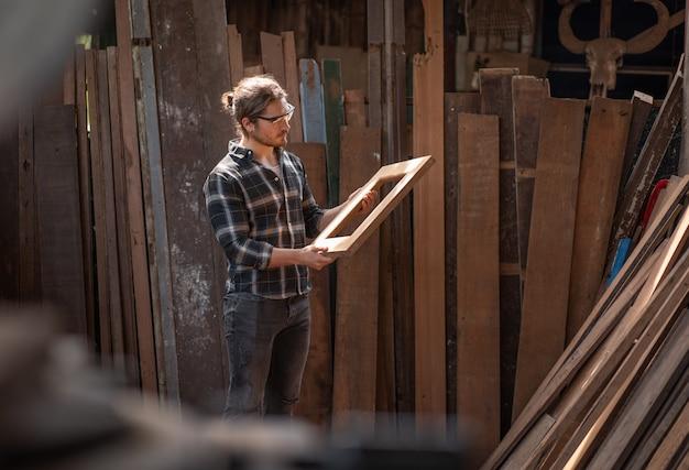 大工のワークショップで木製の立っている窓枠を保持している大工の男