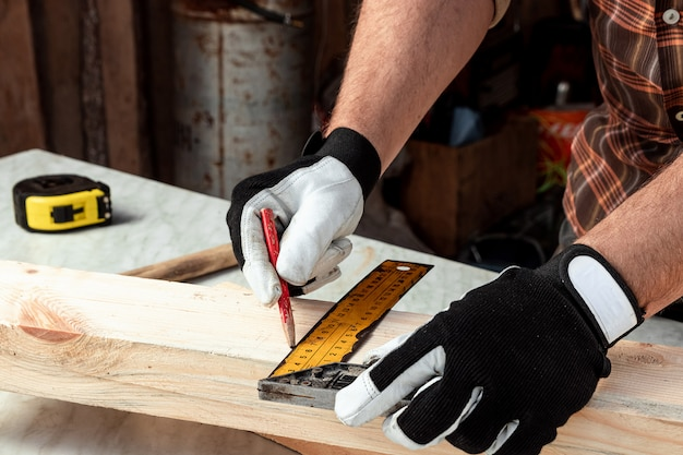 Carpenter man notes with a pencil on the board marks for cutting, male hands with a pencil closeup on a wooden board. woodwork