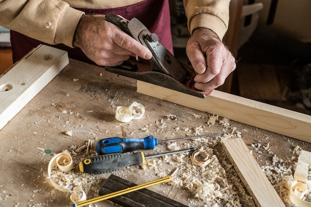 Carpenter man scraping curled wood scraps with hand plane tool and wooden plank.