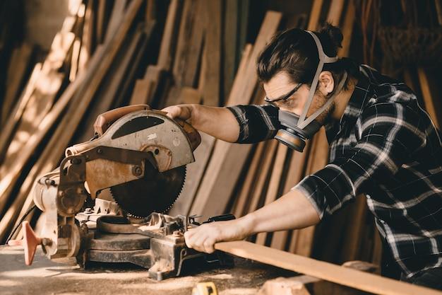 木材工房で保護安全装置を備えた電気ウッドカッターマシンを使用している大工の男
