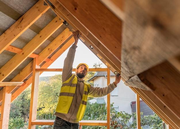 屋根に取り組んでいる大工の男