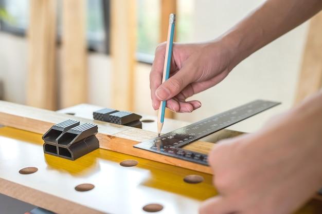 장인 작업장의 판자에 목수 표시 지점, 남자는 자로 나무 판자를 측정하고 연필로 표시합니다