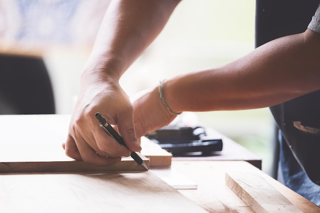 A carpenter measures the planks to assemble the parts, and build a wooden table for the customer