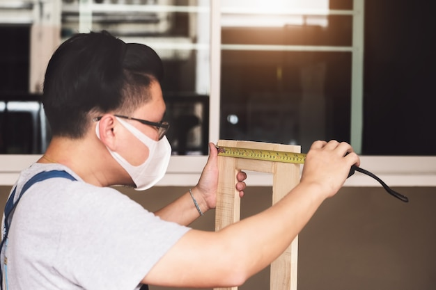 A carpenter measures the planks to assemble the parts and build a wooden table for the customer