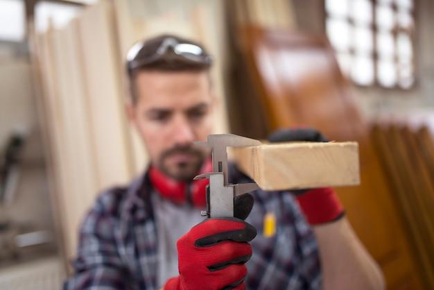 Плотник, измеряющий толщину дощатого древесного материала штангенциркулем для нового проекта