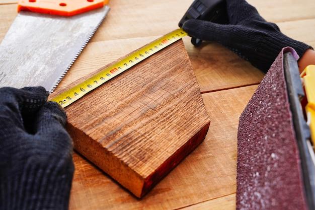 Плотник измеряет деревянную доску на рабочем месте в перчатках, делая изделия ручной работы из дерева