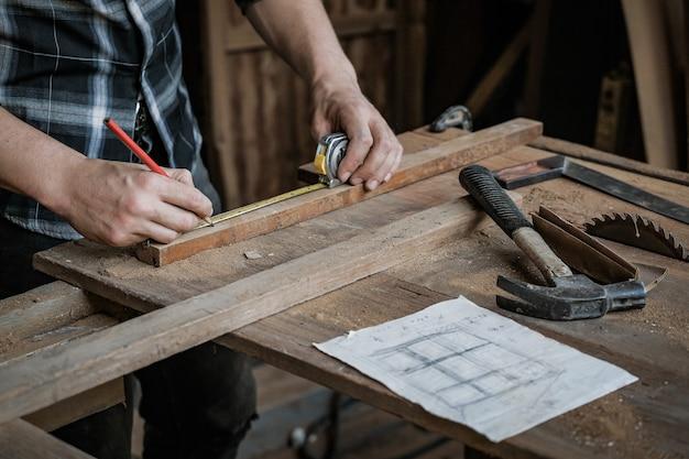 大工の男性は、大工店で木材の測定に取り組んでいます。