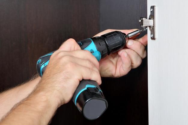 Плотник монтирует шкаф, завинчивание шурупа, петлю мебельной двери с помощью аккумуляторной отвертки.