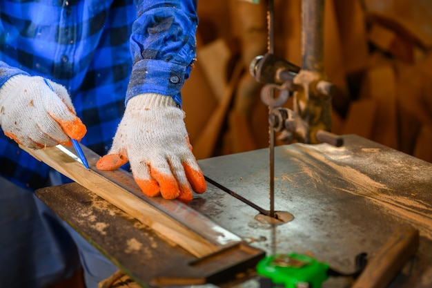 Плотник или мастер используйте циркулярную пилу, чтобы распилить дерево. в мастерской фон офиса плотницких работ.