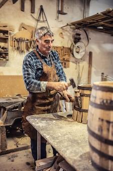 목수는 아늑한 작업장에서 만든 새 나무 통에 금속 줄무늬를 놓습니다.