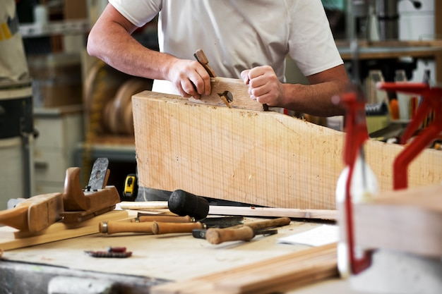 Carpenter planing a block of wood to in workshop
