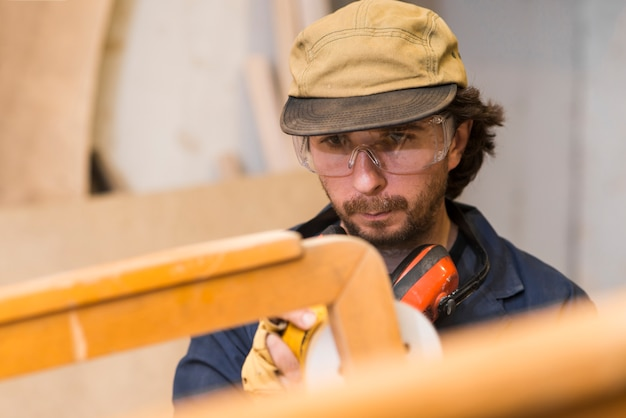 Carpenter polishes wooden furniture with a sander in the workshop