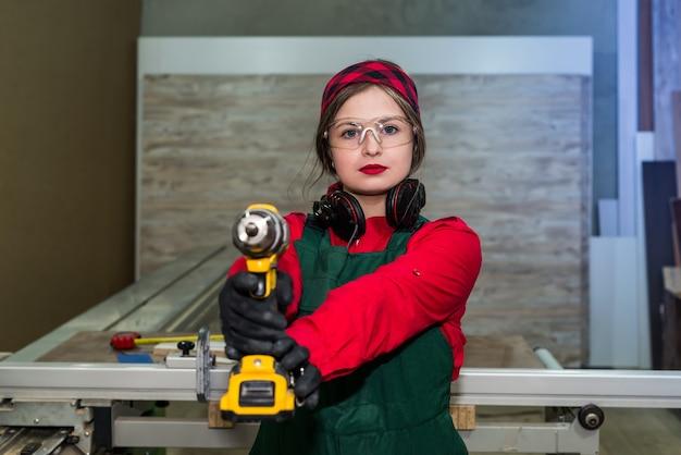 Плотник позирует со сверлильными станками, плотник - женщина