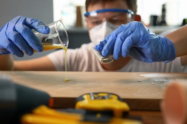 Плотник наливает лак со стеклянной деревянной поверхности.