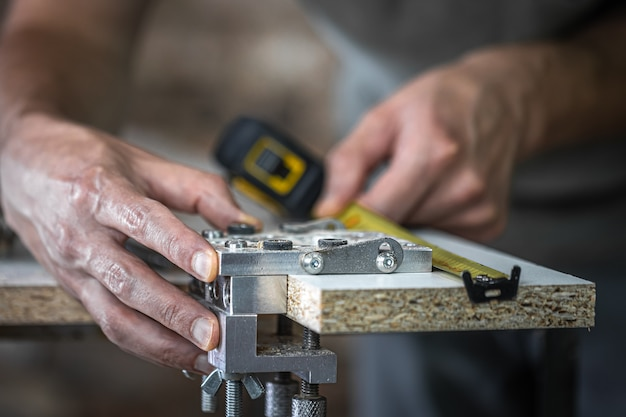 A carpenter in the process, a professional tool for precision drilling in wood.